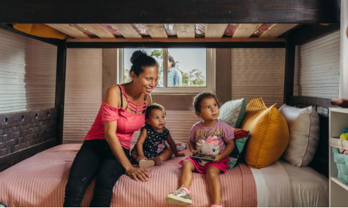 A family sits inside one of the two newly constructed 3D-printed homes in Mexico